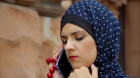 Girl in muslim clothes talking on the phone Стоковые видеозаписи