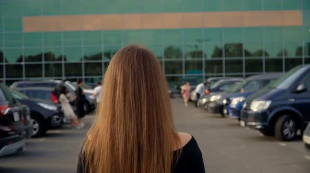 The camera follows a young attractive brunette in the parking lot. Stock mozgókép
