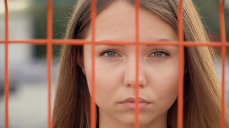 Portrait of a girl on the background of the grid Стоковые видеозаписи