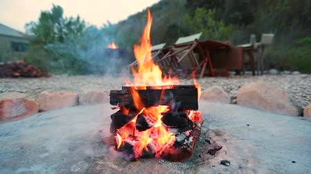 A campfire burns in a fire pit at a camp