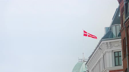 Danish flag waving in the wind on top of a building with clear sky to the side