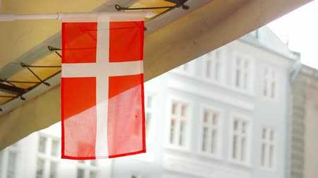 Small Danish flag waving in the wind and rain with buildings in the background