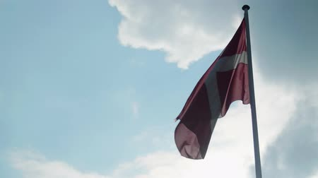Danish flag flying under cloudy skies almost a silhouette Stock Footage