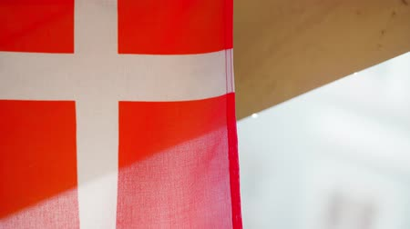 copenhagen : Extreme closeup of Danish flag hanging outside while people walk past Stock Footage