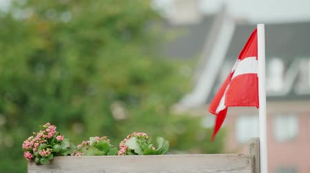 copenhagen : Small Danish flag, attached to a wooden flower bed, waving in the wind and rain