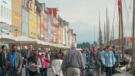 copenhagen : COPENHAGEN - September 2017 - Tourists walking along the Nyhavn Waterfront in Copenhagen, Denmark