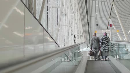 Amsterdam - 2018: Two travelers ride a travelator in Schiphol Airport
