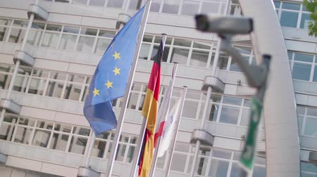 avrupa birliği : EU flags wave behind a cctv security camera on a pole in Berlin Stok Video