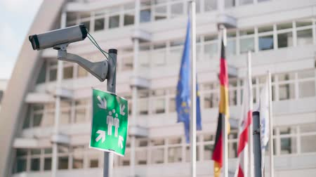 watch tv : CCTV security camera on a pole with a meeting point sign and EU flags behind Stock Footage