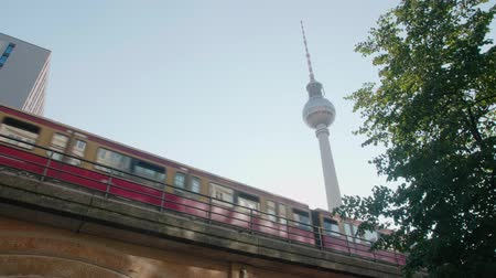 berlin skyline : A train passes in front of the TV tower in Alexanderplatz, Berlin Stock Footage