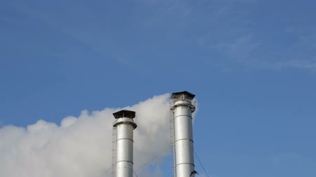 chp : The smoke from the chimneys of the CHP. Pollution of the environment. Environmental disaster. Blue sky.