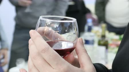 Woman holding a glass of red wine. People clink glasses with drinks at the event. Footage 4K, Ultra HD, UHD