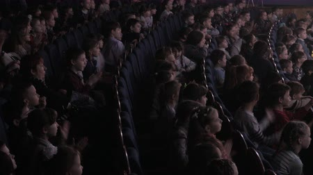 Children applauding in the auditorium during the performance. Theater for young spectators, Russia, Saratov, April 28, 2017. 4k footage clip 影像素材