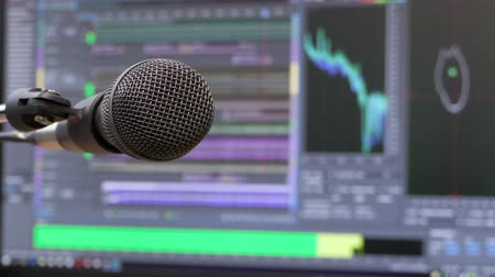 Microphone on the background of the computer monitor. Home recording Studio. Close-up. The focus in the foreground. Blurred background. Software for recording and editing sounds. 4K, UHD, Ultra HD.