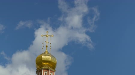 The Golden dome of an Orthodox temple on the background of blue sky and clouds. Golden cross on the dome of the temple. The Holy Trinity Cathedral, Russia, Saratov. Built in the 17th century. Time lapse. 4K, Ultra HD, UHD. 影像素材