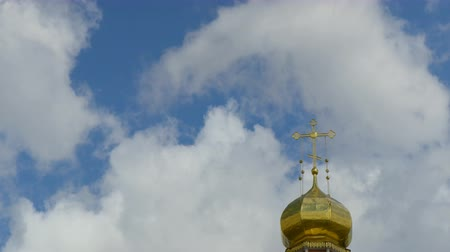 The Golden dome of an Orthodox temple on the background of blue sky and clouds. Golden cross on the dome of the temple. Time lapse. A looped clip with no breaks. 4K, Ultra HD, UHD