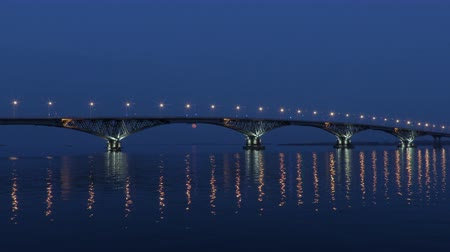 Full moon rises over the bridge. Time-lapse. Road bridge between the cities of Saratov and Engels, Russia. The Volga River. The evening lights of cars and street lights. 4K, Ultra HD
