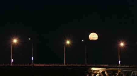 Full moon rises over the bridge. Time-lapse. Road bridge between the cities of Saratov and Engels, Russia