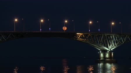 Full moon rises over the bridge. Time-lapse. Road bridge between the cities of Saratov and Engels, Russia. The Volga River. The evening lights of cars and street lights. The reflection in the water. A cargo ship sails under the bridge. 影像素材