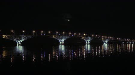 Full moon rises over the bridge. Road bridge between the cities of Saratov and Engels, Russia. The Volga River. The evening lights of cars and street lights. 4K, Ultra HD