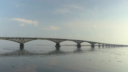 Road bridge between the cities of Saratov and Engels. A river landscape. Spring. Ice drift on the river. Russia, Saratov, the Volga river. Time-lapse recording. Footage in 4K, UHD