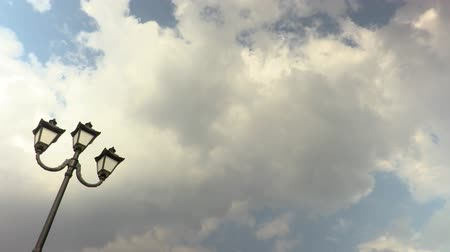 Lamppost against the sky. Clouds running through blue sky. Time-lapse recording. Footage 4K, UHD