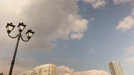 Lamppost and urban architecture. Russia, Saratov. Clouds running through blue sky. Time-lapse recording. Footage 4K, UHD 影像素材