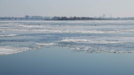 marchs financiers : Ice drift on the Volga river in March. The City Of Saratov, Russia. Road bridge. Sunny day. Blue sky. Birds crows on the ice