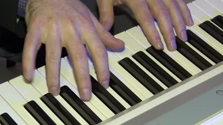 clubhouse : The musician plays on a digital piano. Hands of the pianist. A synthesizer or electronic piano.