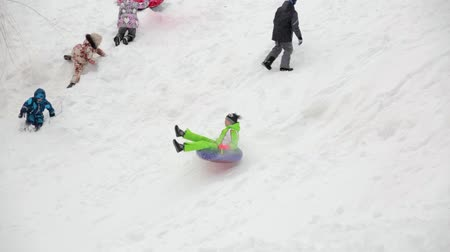 Saratov  Russia - March 8, 2018: Children ride with an ice slide. Winter vacation. Outdoor activity. Winter day in the city Park. 影像素材