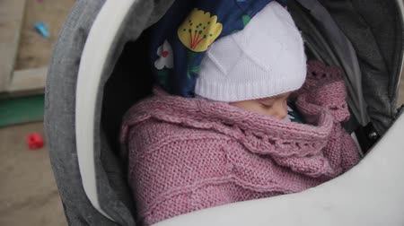 stay active : Newborn sleeps in baby carriage while being pushing back and forth.