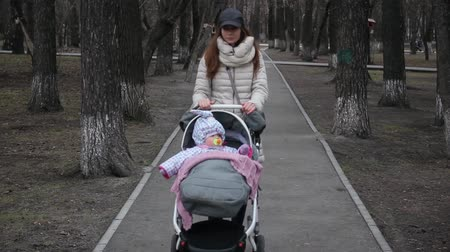 wozek dzieciecy : Beautiful woman walking with her little daughter and pushing push stroller in park.