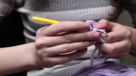 amigurumi : People and needlework concept - woman knitting with crochet hook and pink yarn