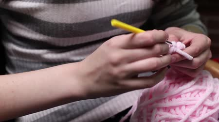 crochet : People and needlework concept - woman knitting with crochet hook and pink yarn