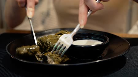 National traditional cuisine food in the restaurant. Woman is eating dolma with sour cream served in clay plate, dish closeup. Girl is eating with fork and knife
