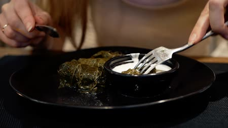 служить : National traditional cuisine food in the restaurant. Woman is eating traditional georgian dolma with sour cream served in clay plate, dish closeup. Girl is eating with fork and knife