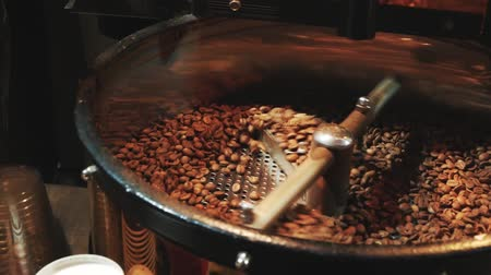 grãos de café : Mixing roasted coffee. Roasting coffee beans at Roasting equipment. Coffee beans are spinning in a machine