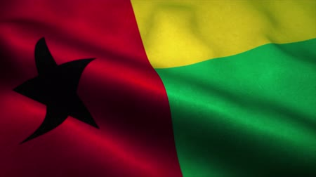 эмблема : Guinea Bissau flag waving in the wind. National flag of Guinea Bissau. Sign of Guinea Bissau seamless loop animation. 4K