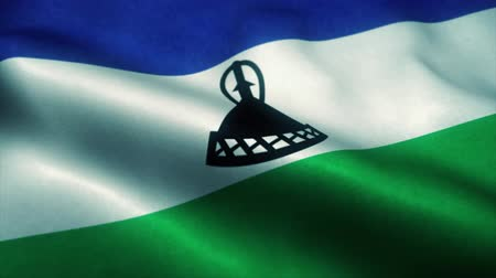 эмблема : Lesotho flag waving in the wind. National flag of Lesotho. Sign of Lesotho seamless loop animation. 4K