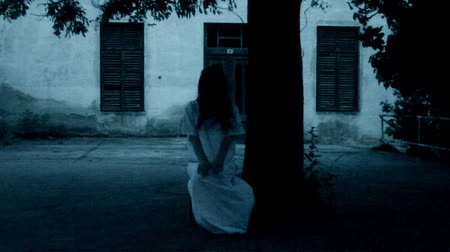 vento : Mysterious scary woman in white dress sitting under the tree Vídeos