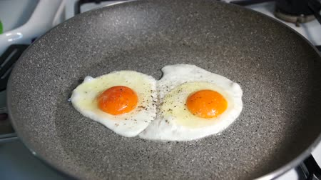 ovo : Two fried egg yolks fried in a stone pan on a gas stove