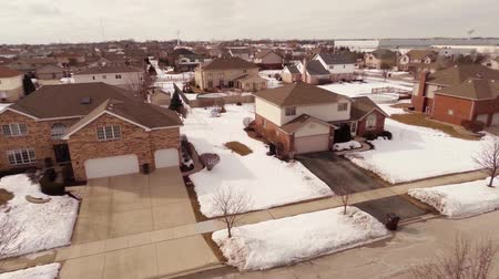 dom : Overhead aerial view of residential houses and yards along suburban street covered in snow