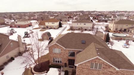 exterior : Overhead aerial view of residential houses and yards along suburban street covered in snow