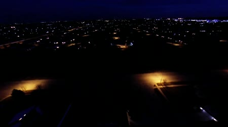 subúrbio : Night view of house lights, streets and buildings from aerial in air flight above ground