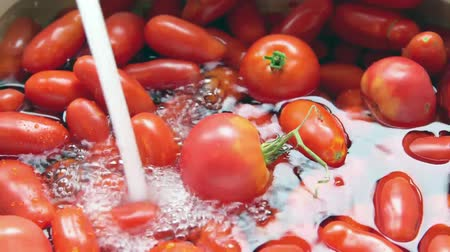 овощи : Washing fresh tomatoes under tap water from kitchen sink