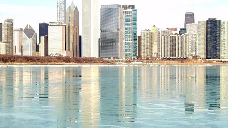 reflexionando : Horizonte de Chicago, Illinois refleja en el Lago Michigan agua helada Archivo de Video