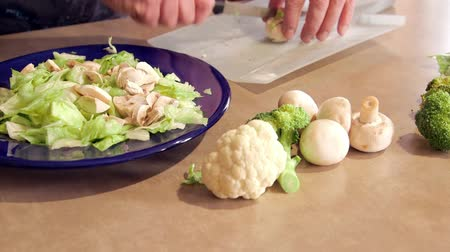 Man preparing dinner salad cutting lettuce and fresh vegetables with a knife Vídeos