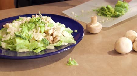 salata : Man preparing dinner salad cutting lettuce and fresh vegetables with a knife Stok Video
