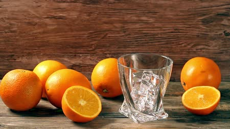 pijany : Pouring whiskey from bottle to glass over gray background with orange Wideo