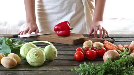 bordo : Woman slice vegetables. Woman slice paprika on wooden table. Rustic style. Stock Footage